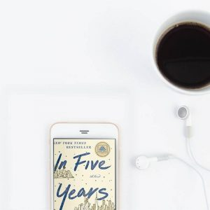 Light But Smart Audiobooks for Easy Summer Listening - a coffee cup and phone with In Five Years audiobook on the screen